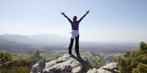 Woman standing on mountain with arms stretched out
